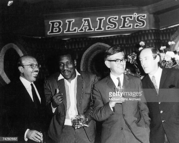 Ahmet Ertegun and Otis Redding pose for a portrait with some other men at Blaise's Club in 1967 in London England