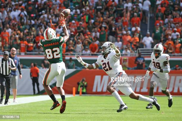Ahmmon Richards of the Miami Hurricanes catches the ball in front of Juan Thornhill of the Virginia Cavaliers on November 18, 2017 at Hard Rock...