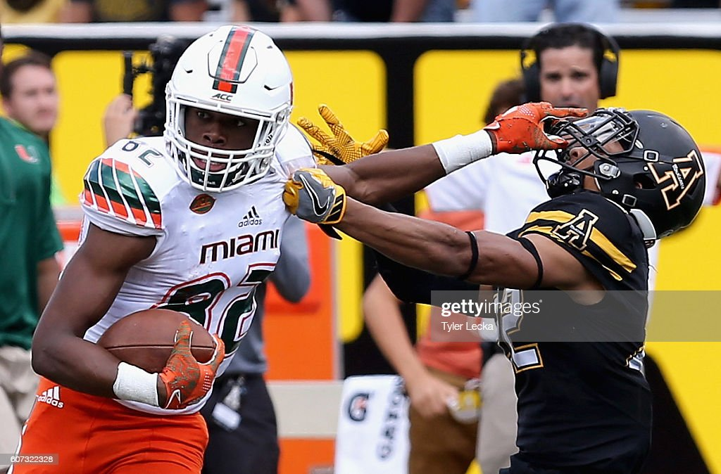 Ahmmon Richards #82 of the Miami Hurricanes tries to break a tackle by Clifton Duck #22 of the Appalachian State Mountaineers during their game at Kidd Brewer Stadium on September 17, 2016 in Boone, North Carolina.