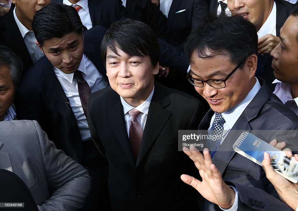 Ahn Cheol Soo, chairman of Ahnlab Inc., center, leaves a news conference after announcing his presidential candidacy in Seoul, South Korea, on Wednesday, Sept. 19, 2012. Ahn, founder of South Korea's biggest antivirus software maker, said he will run as an independent in the December presidential race to succeed Lee Myung Bak. Photographer: SeongJoon Cho/Bloomberg via Getty Images