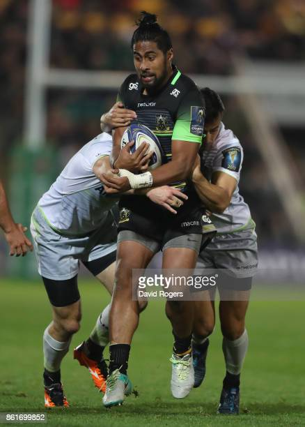 Ahsee Tuala of Northampton is tackled by Duncan Taylor and Alex Lozowski during the European Rugby Champions Cup match between Northampton Saints and...
