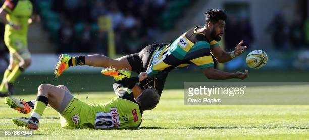 Ahsee Tuala of Northampton off loads the ball as Mathew Tait tackles during the Aviva Premiership match between Northampton Saints and Leicester...