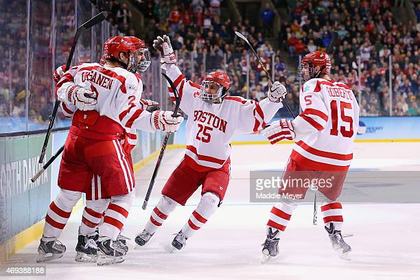 Ahti Oksanen Brandon Fortunato and Nick Roberto celebrate after Cason Hohmann of the Boston University Terriers scored against the Providence Friars...