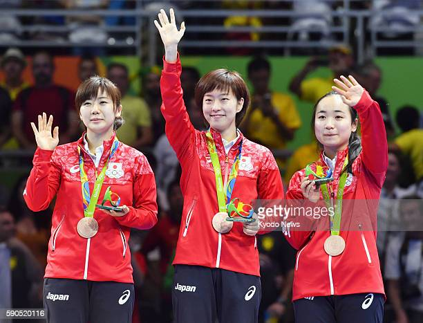 Ai Fukuhara Kasumi Ishikawa and Mima Ito wave to the audience after receiving their bronze medals at the awards ceremony for the women's table tennis...