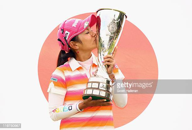Ai Miyazato of Japan celebrates with the trophy after her victory at the Evian Masters at the Evian Masters Golf Club on July 24 2011 in...