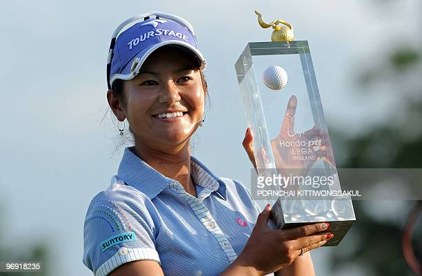 Ai Miyazato of Japan holds with winner's trophy following her victory in the final round of the Golf Honda PTT LPGA Thailand 2010 golf tournament at...