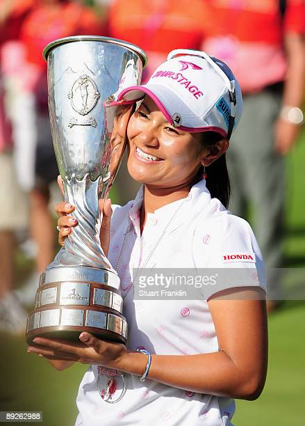 Ai Miyazato of Japan poses with the winners trophy after winning in a playoff against Sofie Gustafson of Sweden after the final round of the Evian...