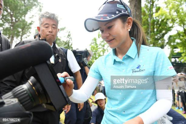 Ai Miyazato of Japan signs an autograph on the TV camera during the final day of the Suntory Ladies Open at the Rokko Kokusai Golf Club on June 11...
