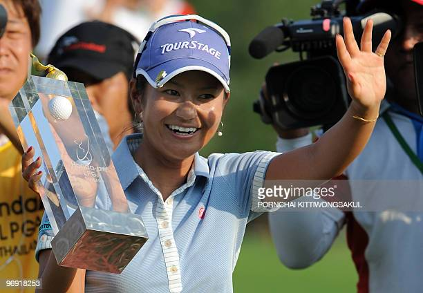 Ai Miyazato of Japan waves to fans as he holds with winner's trophy following her victory in the final round of the Golf Honda PTT LPGA Thailand 2010...