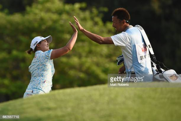 Ai Suzuki of Japan celebrates with her caddie on the 18th green after hitting out of the bunker for a birdie during the second round of the...