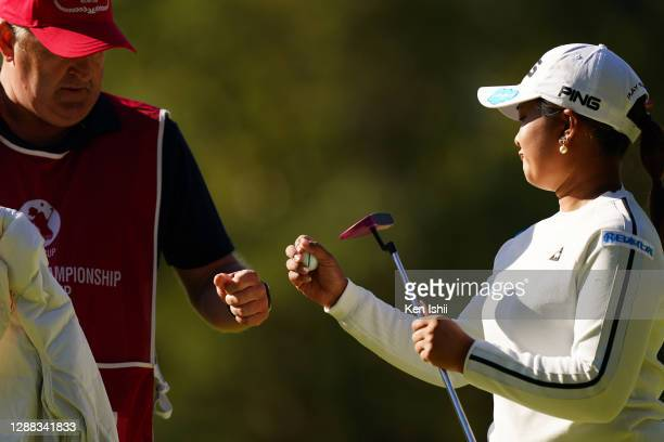 Ai Suzuki of Japan fist bumps with her caddie after the birdie on the 1st green during the final round of the JLPGA Tour Championship Ricoh Cup at...