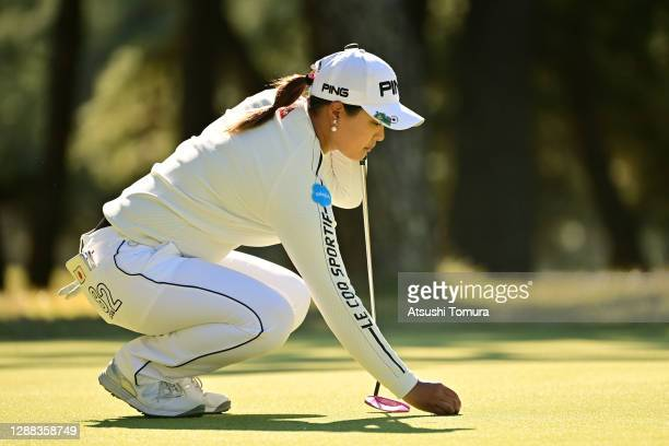 Ai Suzuki of Japan places the ball on the 5th green during the final round of the JLPGA Tour Championship Ricoh Cup at the Miyazaki Country Club on...