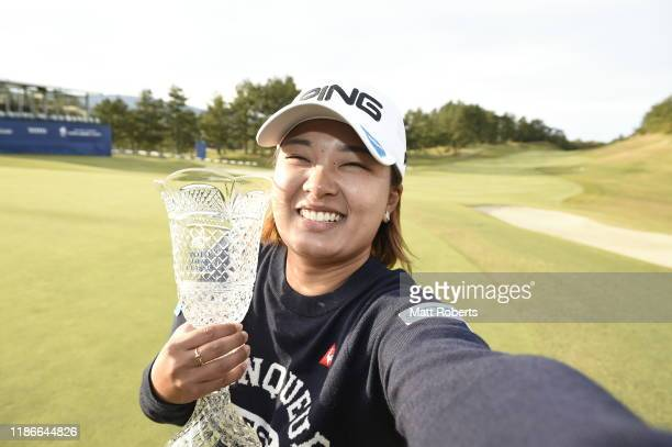 Ai Suzuki of Japan pretends to take a selfie while holding the trophy on the 18th green after winning the final round of the TOTO Japan Classic at...