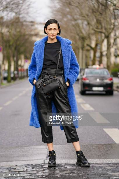 Ai Tominaga wears a blue fluffy long coat, a black t-shirt, a Ralph Lauren crossbody bag, black leather cropped pants, leather shoes, outside Akris,...
