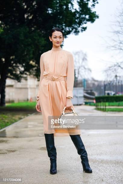 Ai Tominaga wears a pale pink flowing dress, golden bracelets, a white Chloe bag, black leather long boots, outside Chloe, during Paris Fashion Week...