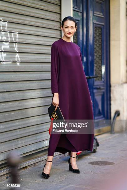 Ai Tominaga wears a purple dress a black Valentino bag outside Valentino during Paris Fashion Week Haute Couture Fall/Winter 2019/2020 on July 03...