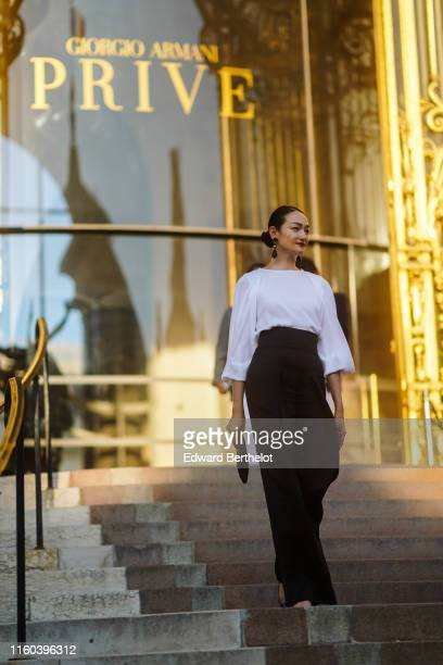 Ai Tominaga wears earrings a white blouse black widelegs pants a black clutch outside Armani during Paris Fashion Week Haute Couture Fall/Winter...