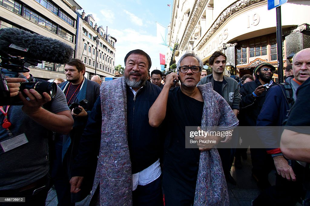 Ai Weiwei (L) and Anish Kapoor depart the Royal Academy as they walk through the city as part of a march in solidarity with migrants currently crossing Europe on September 17, 2015 in London, England. Each artist carried a single blanket symbolizing the needs that face migrants coming to Europe.