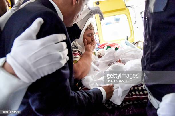 Aicha the mother of Algerian poprai star and singer Rachid Taha bids him farewell in an ambulance during his funeral in the town of Sig in Agleria's...
