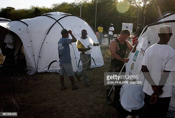 Aid and army workers pitch tents for refugees from PortauPrince following the January 12 earthquake that destroyed the city as in a field in...