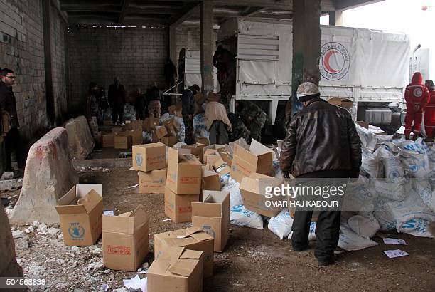 Aid parcels and boxes are offloaded from vehicles in a warehouse in Idlib in northwestern Syria on January 11 2016 The Syrian Arab Red Crescent said...
