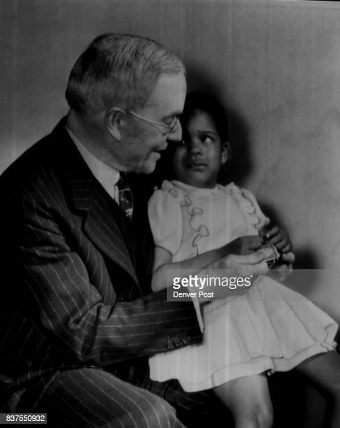Aid United Negro College FundJohn D Rockefeller Jr National chairman of the United Negro College Fund holds 4yearold Marietta Dockery on his lap...