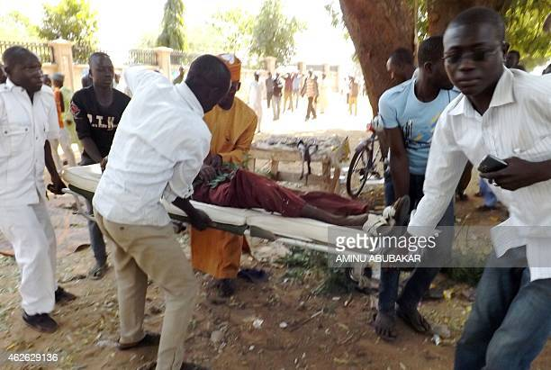 Aid workers evacuate a man injured in a suicide blast in the northeastern Nigerian city of Potiskum on February 1 2015 A suicide bomb attack...