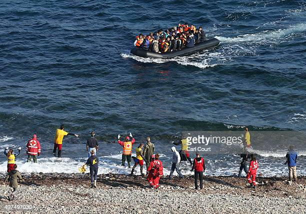 Aid workers gesture at a migrant boat as it approaches shore after making the crossing from Turkey to the Greek island of Lesbos on November 17 2015...