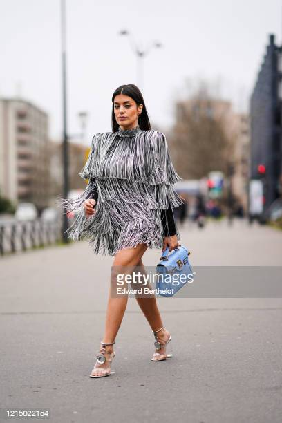 Aida Domenech wears a black and white fringed turtleneck dress, a blue Balmain bag, silver bejeweled shoes, outside Balmain, during Paris Fashion...