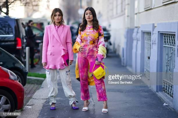 Aida Domenech wears a pink and yellow MSGM top, a colorful knit coat, hot pink crop pants, a yellow bag, white heeled mules ; Angela Rozas Saiz wears...