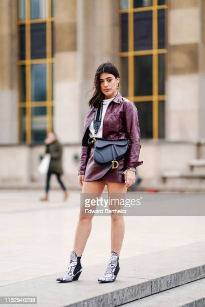 Aida Domenech wears a purple leather jacket, a Dior Saddle bag, leather skirt, snake print shoes, outside Ann Demeulemeester, during Paris Fashion...