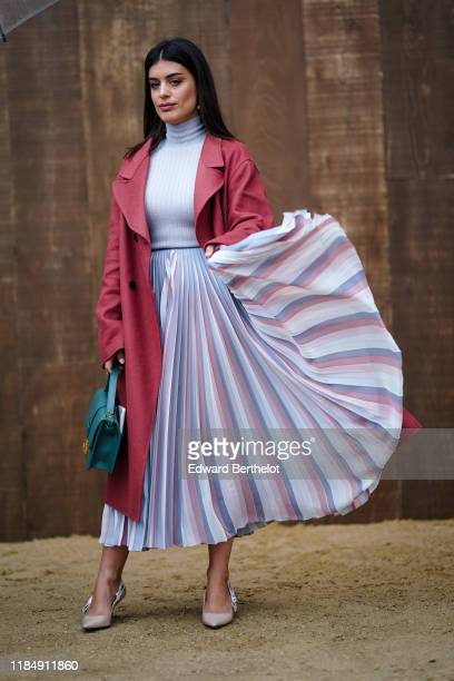 Aida Domenech wears a red trench coat a pale blue turtleneck pullover a pleated skirt a green bag outside Dior during Paris Fashion Week Womenswear...
