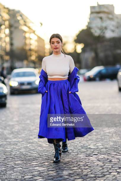 Aida Domenech wears a white cropped top, a blue jacket, a blue pleated skirt, black leather shiny boots, outside Rochas, during Paris Fashion Week -...