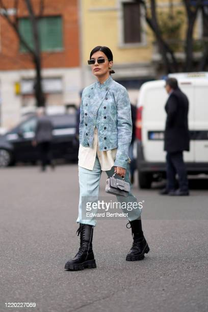 Aida Domenech wears sunglasses, a blue double breasted jacket with several buttons, a white top, blue lustrous pants, black leather boots, a silver...