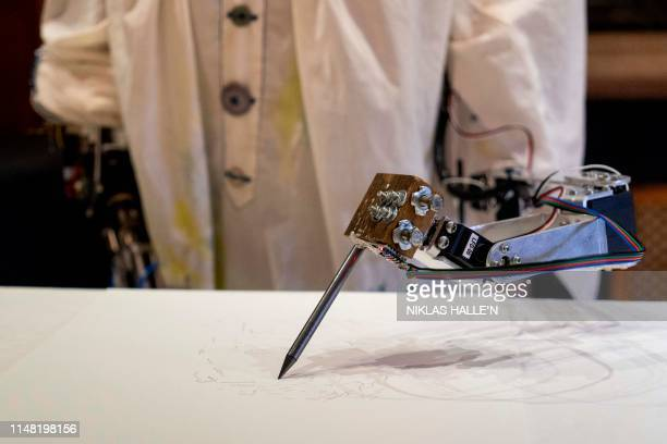 AiDa the AI humanoid robot artist draws a portrait of her creator Aidan Meller during a demonstration at a launch event for its first solo exhibition...