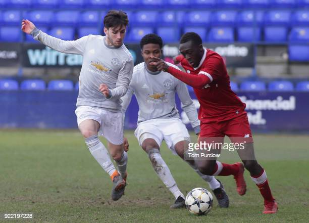 Aidan Barlow and Tyrell Warren of Manchester United U19s in action with Bobby Adekanye of Liverpool U19s during the UEFA Youth League match between...