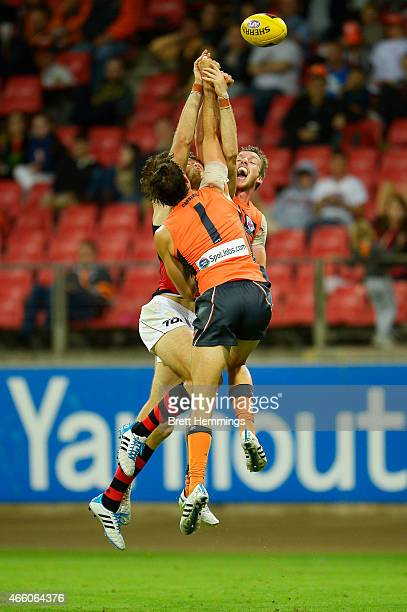 Aidan Corr and Phil Davis of the Giants contest a high ball with Jonathan Giles of the Bombers during the NAB Challenge AFL match between the Greater...
