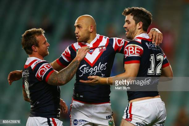 Aidan Guerra of the Roosters is congratulated by Blake Ferguson and Jakob Friend of the Roosters after scoring a try during the round 24 NRL match...