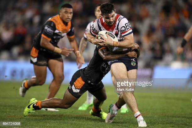 Aidan Guerra of the Roosters is tackled during the round 14 NRL match between between the Wests Tigers and the Sydney Roosters at Campbelltown Sports...