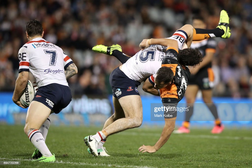 Aidan Guerra of the Roosters picks up and tackles Jack Littlejohn of the Tigers during the round 14 NRL match between between the Wests Tigers and the Sydney Roosters at Campbelltown Sports Stadium on June 11, 2017 in Sydney, Australia.
