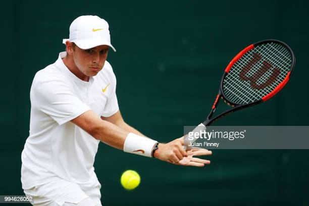 Aidan McHugh of Great Britain plays a backhand in his Boys' Singles first round match on day seven of the Wimbledon Lawn Tennis Championships at All...