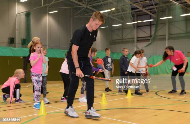 Aidan McHugh of Great Britain with local children during a tennis activity session on the fourth day of The Glasgow Trophy at Scotstoun Leisure...
