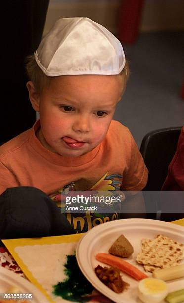 Aidan Selzer age 3 wears his yamulke and stares at his Seder Plate wondering which food to eat first as the two and three year olds have a Seder at...