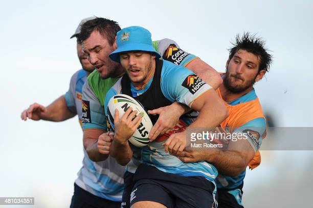 Aidan Sezer is tackled during a Gold Coast Titans NRL training session at Tugun Rugby League Field on March 28 2014 on the Gold Coast Australia