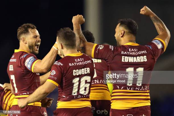 Aidan Sezer of Huddersfield Giants celebrates with team mates Jack Cogger and Kenny Edwards after victory in the Betfred Super League match between...