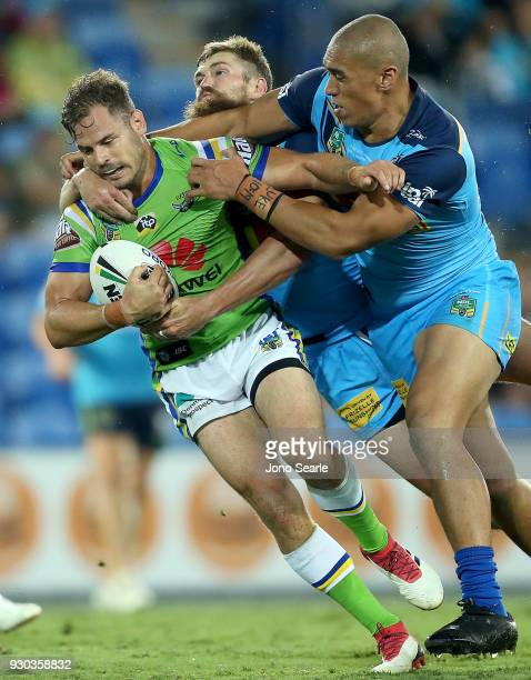 Aidan Sezer of the Raiders is tackled during the round one NRL match between the Gold Coast Titans and the Canberra Raiders at Cbus Super Stadium on...