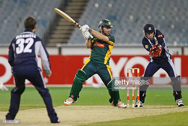 Aiden Blizzard of the Tigers bats in front of wicket keeper Peter Hanscombe of the Bushrangers during the Ryobi One Day Cup match between Victorian...