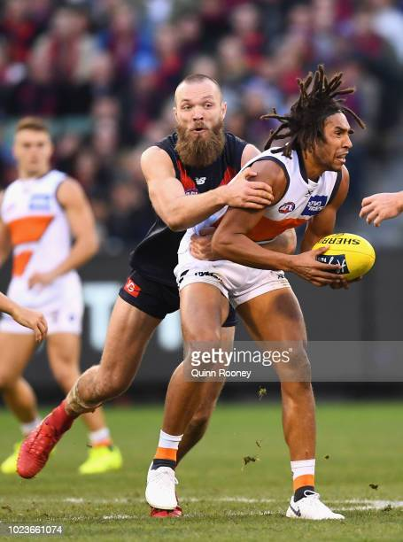 Aiden Bonar of the Giants handballs whilst being tackled by Max Gawn of the Demons during the round 23 AFL match between the Melbourne Demons and the...