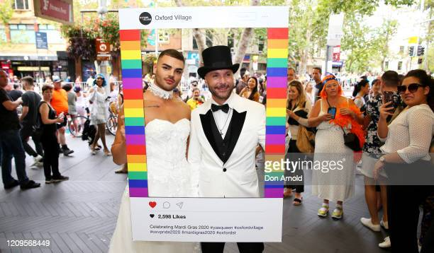 Aiden Eric and Gavin Haughain pose as locals look on during the 2020 Sydney Gay Lesbian Mardi Gras Parade on February 29 2020 in Sydney Australia The...