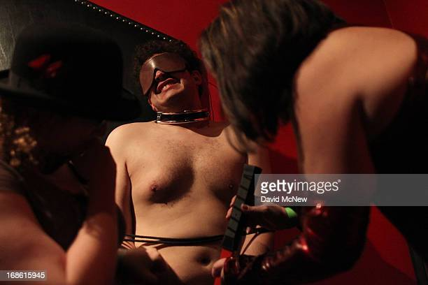 Aiden reacts to electric shocks as he is voluntarily dominated by women at a dungeon party during the domination convention DomConLA in the early...